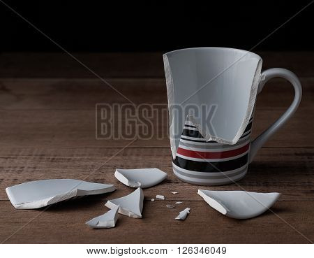 Close up of broken cup on wooden background