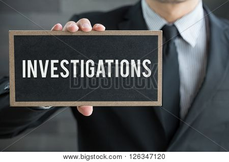 Investigations message on blackboard and hold by businessman businese concept