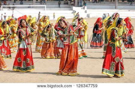 PUSHKAR INDIA - NOVEMBER 21: An unidentified Indian girls in colorful ethnic attire dancing at Pushkar fair.