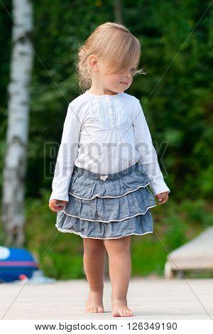 Little girl walking barefoot on pier outdoors