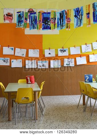 Kindergarten Class With The Chairs And Many Children's Drawings On The Walls