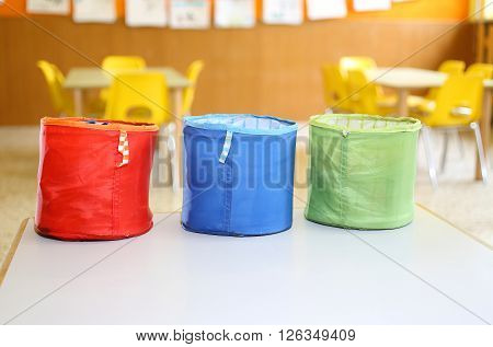 Three Colored Fabric Containers For Children's Toys In The Kindergarten