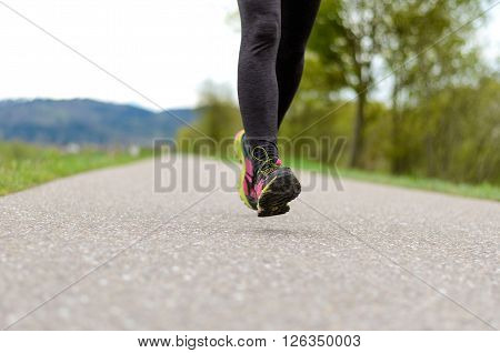 Woman Wearing Tights Jogging On A Country Road