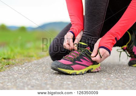 Woman Bending Down To Tie Her Laces