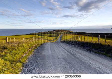 Road to the lighthouse with sheep farm at the left and right side of the road.