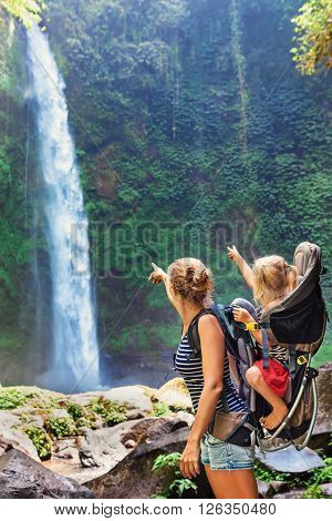 In waterfall pool young happy mother hold little traveller - baby girl in carrying backpack on back. Travel adventure hiking activity with child. Lifestyle on family summer vacation and weekend tour