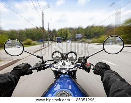 Man driving on moto on big speed on asphalt road
