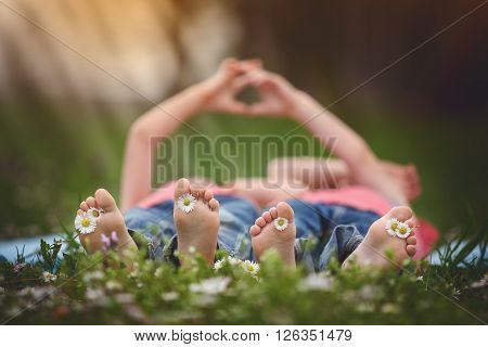 Happy Little Children, Lying In The Grass, Barefoot, Daisies Around Them