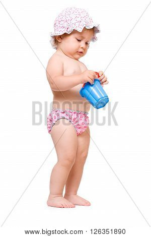 Cute baby girl in swimming pants and sunhat playing, isolated over white background