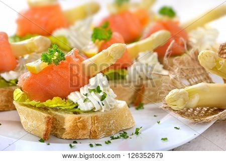 Delicious canapes with German white asparagus, cream cheese with herbs, smoked salmon on Italian ciabatta bread with lettuce leaves