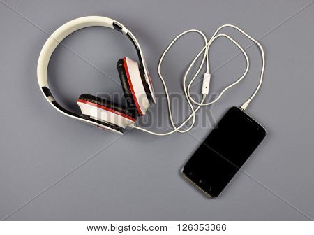 Entertainment today's youth.Close-up of smart phone with headphones on a gray background. (Top view). Listen to music.