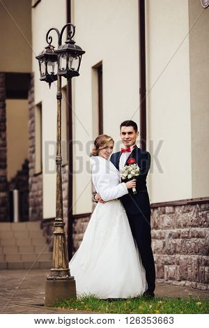 Portrait of a bride and stylish groom lovely standing on the city street near the streetlight holding hands