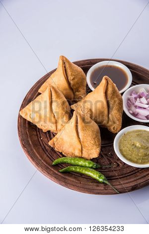 samosa snack with imli chutney or tamarind sauce, onion and green fried chili, served in wooden bowl