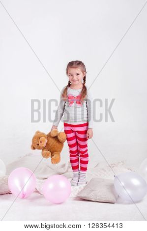 Cute kid girl 3-4 year old playing with teddy bear in room over white. Looking at camera. Childhood. Playful.