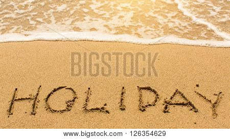 Holiday - inscription by hand on yellow beach sand.