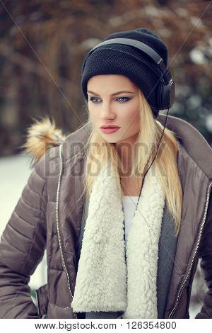Blonde woman in winter cap listening music outdoor portrait