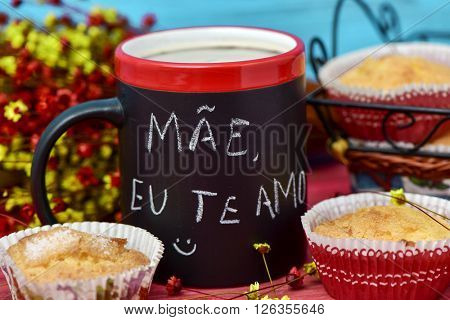 the sentence mae eu te amo, I love you mom in portuguese handwritten with chalk in a black mug with coffee, with some muffins in the background in a set table for breakfast