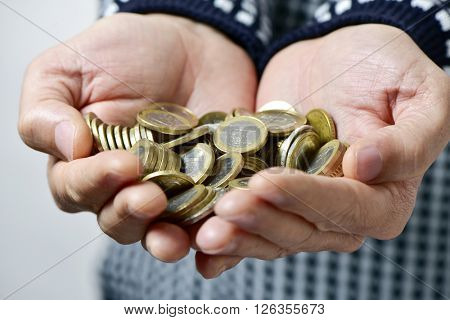 closeup of a young caucasian man with many euro coins in his hands