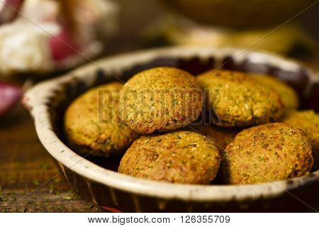 closeup of an earthenware plate with some falafel on a rustic wooden table