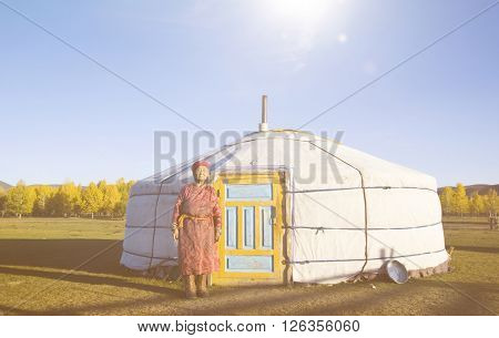 Mongolian lady standing in front of the tent in scenic view.
