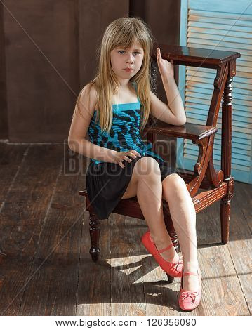Girl 6 years old in dress sits on a chair near the blue wall