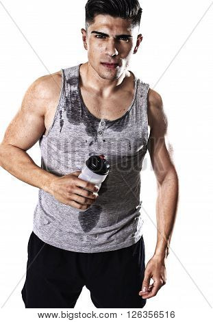 portrait of young athletic sport man thirsty holding bottle of water with sweaty face and wet singlet after refreshing and recovering after hard training workout in hydration concept