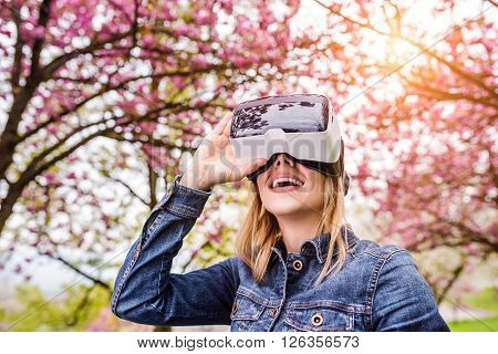 Blond woman wearing virtual reality goggles outside in spring nature ** Note: Visible grain at 100%, best at smaller sizes