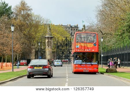 EDINBURGH SCOTLAND - APRIL 16 2016: Tourist sightseeing bus tour of landmarks in the city of Edinburgh Scotland. The bus is at the entrance to Holyrood Park.
