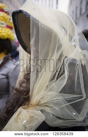 NEW YORK - MAR 27 2016: A woman wearing a bee keeper Easter bonnet made of yellow netting walks on 5th Avenue on Easter Sunday for the traditional Easter Bonnet Parade in Manhattan on March 27, 2016.