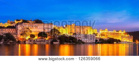 Panorama of famous romantic luxury Rajasthan indian tourist landmark - Udaipur City Palace in the evening - panoramic view. Udaipur, India