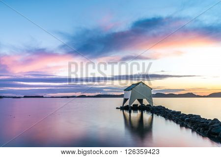 Old boat house along the coast under a pastel sunset
