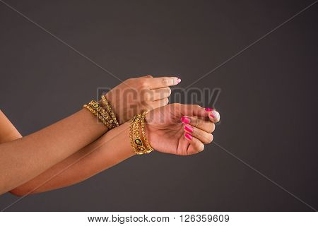 gold bangles in hand, graceful poses of girls hand wearing gold bangles, designer gold bangles and hand, girls hands with golden bangles, closeup, isolated on gray background