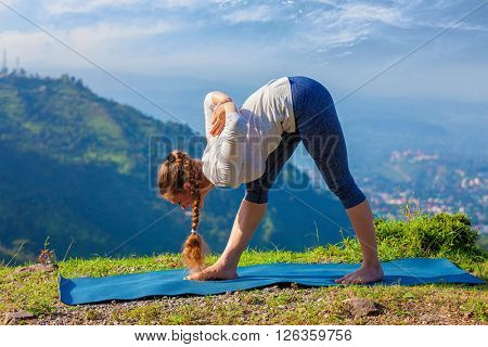 Woman doing Ashtanga Vinyasa yoga asana Parsvottanasana intense side stretch pose  outdoors in mountains Himalayas in the morning. Himachal Pradesh, India