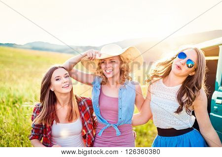 Three teenage hipster girls on a roadtrip. Young friends outside on a summer day