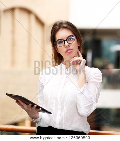 Young business woman in glasses with a tablet standing indoors