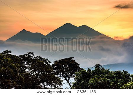 Sunset view of Fuego volcano & Acatenango volcano near Spanish colonial town & UNESCO World Heritage Site of Antigua, Guatemala, Central America