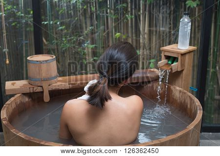 Onsen series : Unrecognizable woman in wooden bathtub