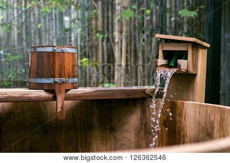 Onsen series : Streaming of hot mineral water and wooden bucket on wooden bathtub