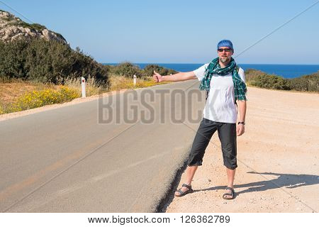 Bearded man with backpack travels hitchhiking alone on the road leading to the sea. Sunny day on the coast.