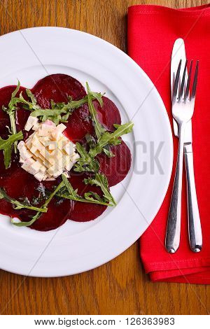 beet salad and cheese and arugula in a white plate