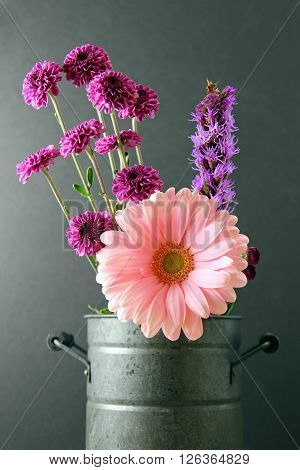 A vase with pink Gerber Daisy and purple small chrysanthemums on a moody background selective focus.