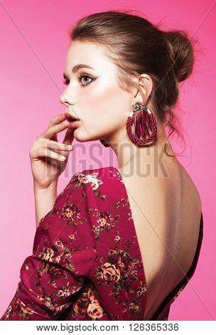 Fashion photo of pretty young woman in pink dress. Studio photo
