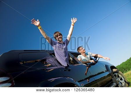 Funny young people looking out the window black car