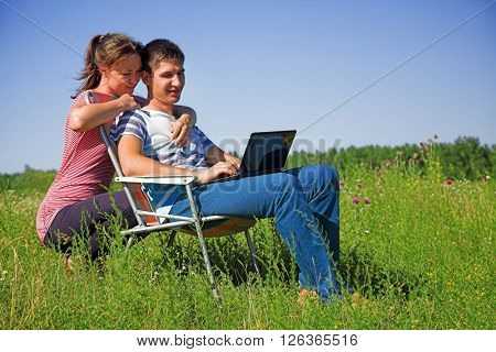 Young couple on the nature watching in a laptop