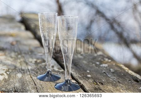 Pair of Plastic Glasses on Wooden Table Outdoor