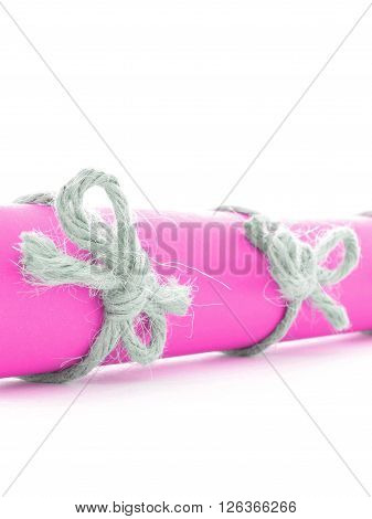 Natural handmade rope knots tied on pink letter roll isolated