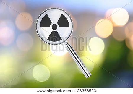 Magnifying lens over background with Radiation symbol, with the blurred lights visible in the background. 3d Rendering.