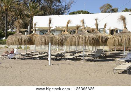 MARBELLA, SPAIN - APRIL 9, 2016: Woman sunbathing and reading in a hammock in the beach of Marbella Spain.