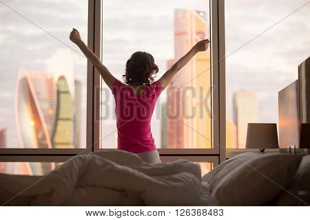 Back view of young woman stretching after early wakeup or doing morning exercises. Beautiful female model relaxing after good night sleep and looking at city scenery in window at dawn