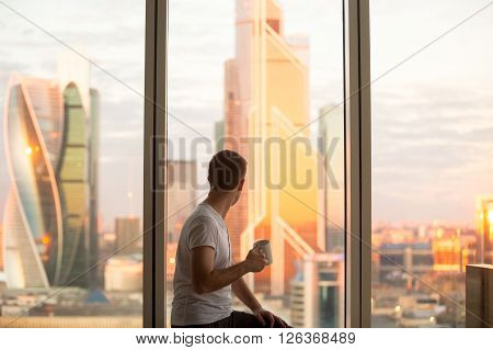 Man Watching Sunrise In Window